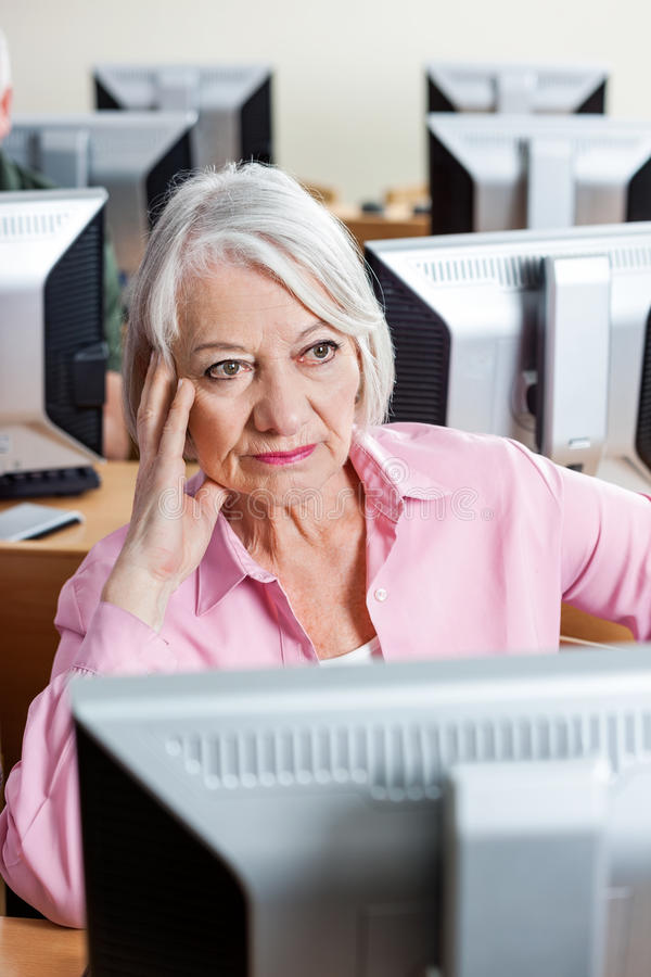 Mujer mayor pensativa que se sienta en el escritorio del ordenador en sala de clase fotografía de archivo