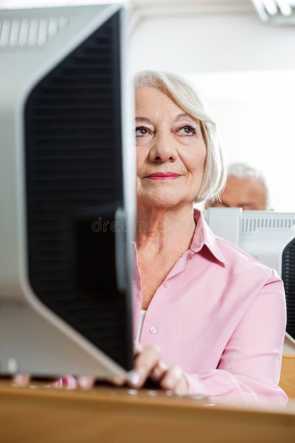 Mujer mayor pensativa que usa el ordenador en sala de clase foto de archivo