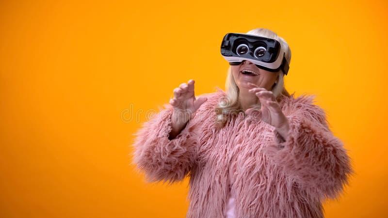 Mujer mayor positiva en capa divertida y las auriculares de VR que juegan tecnología del videojuego fotos de archivo libres de regalías