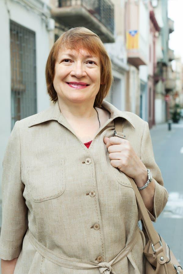 Mujer mayor positiva en la calle europea de la ciudad foto de archivo