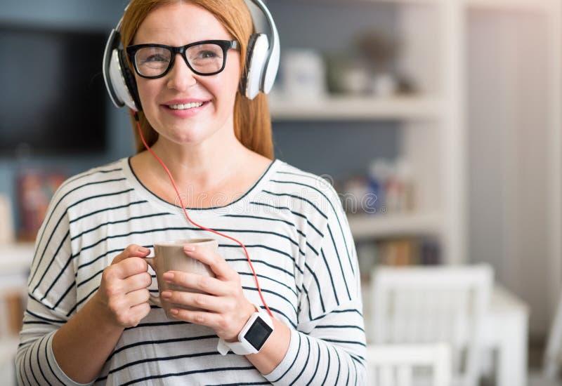 Mujer mayor positiva que escucha la música fotografía de archivo libre de regalías
