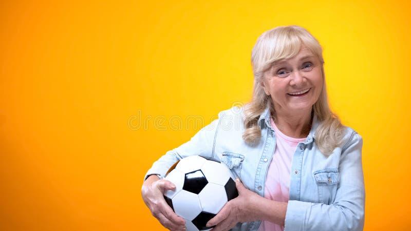 Mujer mayor positiva que lleva a cabo el balón de fútbol, la energía de la vida y el fondo de la vivacidad imagen de archivo libre de regalías