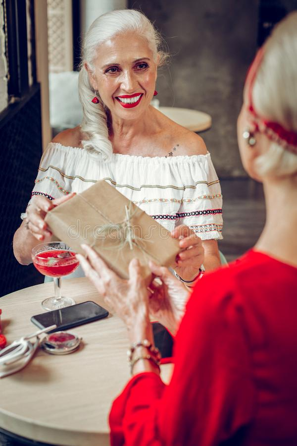 Mujer mayor positiva que saluda a su mejor amigo imagen de archivo libre de regalías