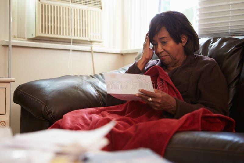 Mujer mayor preocupante que se sienta en Sofa Looking At Bills fotografía de archivo libre de regalías