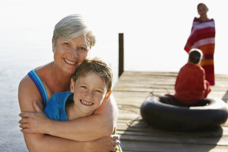 Mujer mayor que abraza al nieto en el embarcadero foto de archivo