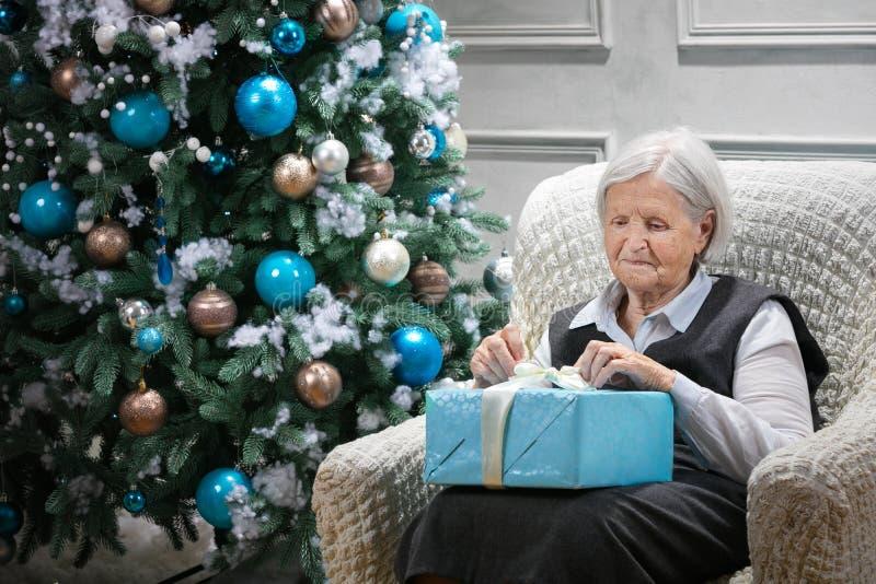 Mujer mayor que abre un paquete con un regalo fotos de archivo