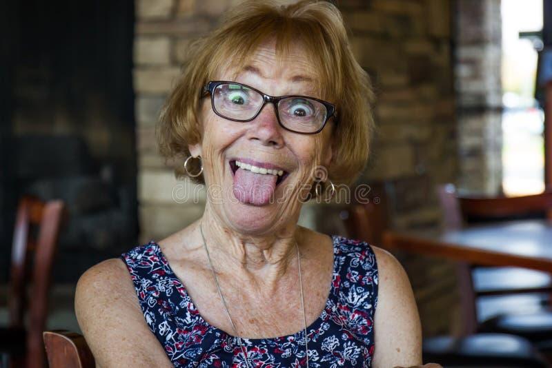 Mujer mayor que actúa tonta foto de archivo