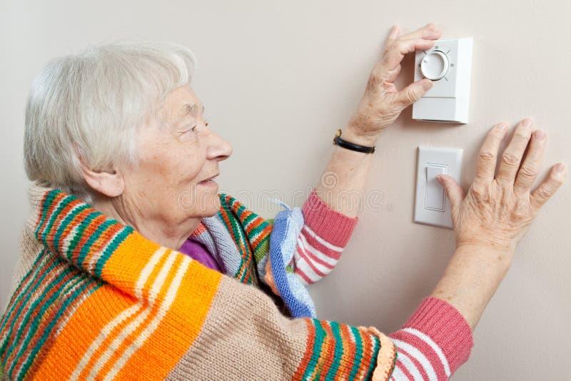 Mujer mayor que ajusta su termóstato fotos de archivo