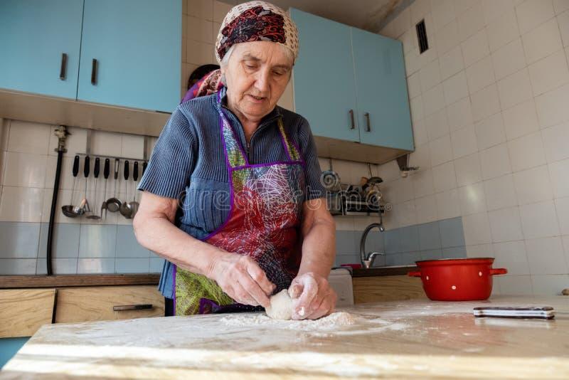 Mujer mayor que amasa la pasta en su cocina casera fotografía de archivo