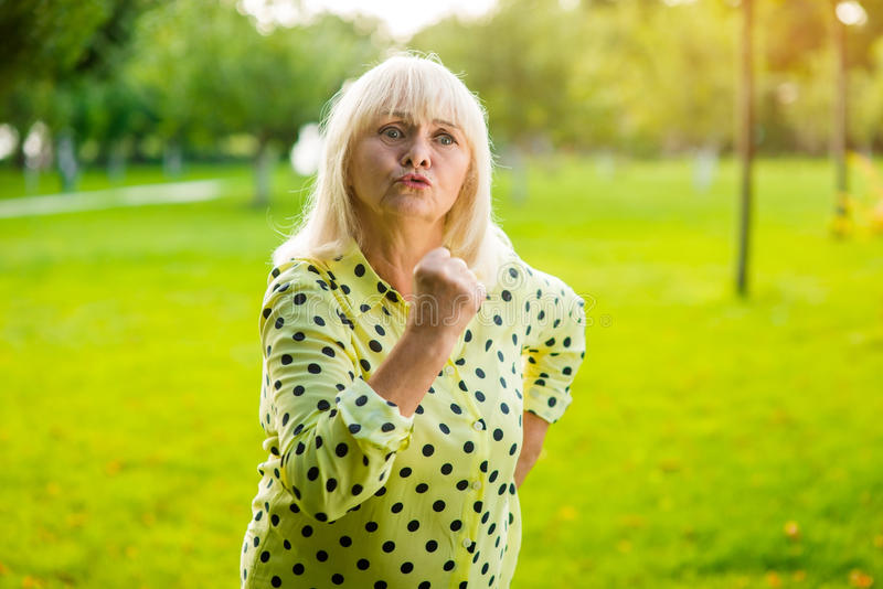 Mujer mayor que amenaza con el puño foto de archivo libre de regalías