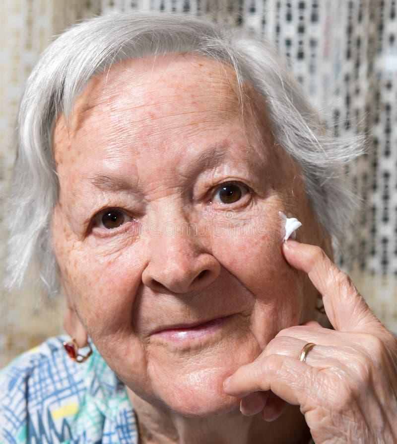 Mujer mayor que aplica la crema antienvejecedora fotos de archivo libres de regalías