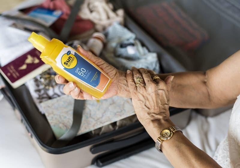 Mujer mayor que aplica la protección solar en su brazo imagenes de archivo
