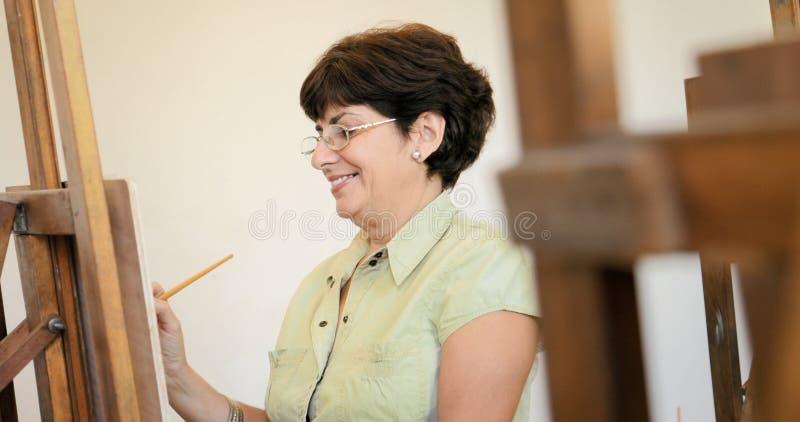 Mujer mayor que aprende pintar en Art Lesson imágenes de archivo libres de regalías