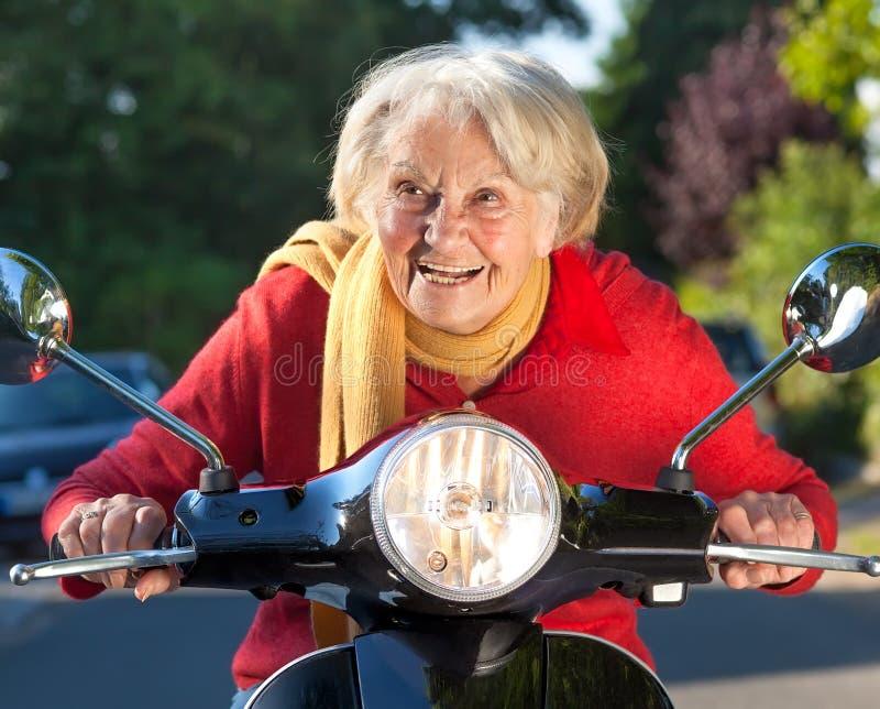 Mujer mayor que apresura en una vespa imagenes de archivo