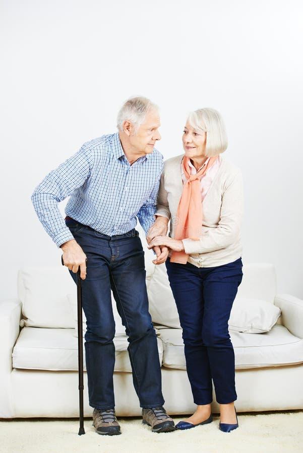 Mujer mayor que ayuda al hombre mayor que se levanta fotos de archivo