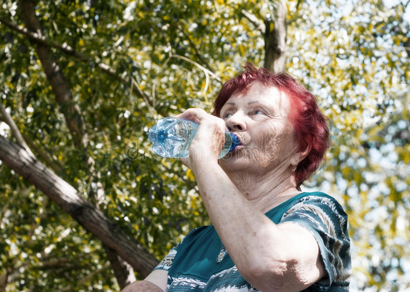 Mujer mayor que bebe el agua mineral imagen de archivo libre de regalías