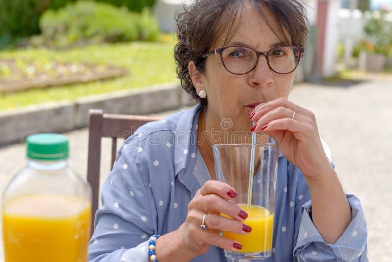 Mujer mayor que bebe el zumo de naranja en su jardín imagen de archivo libre de regalías