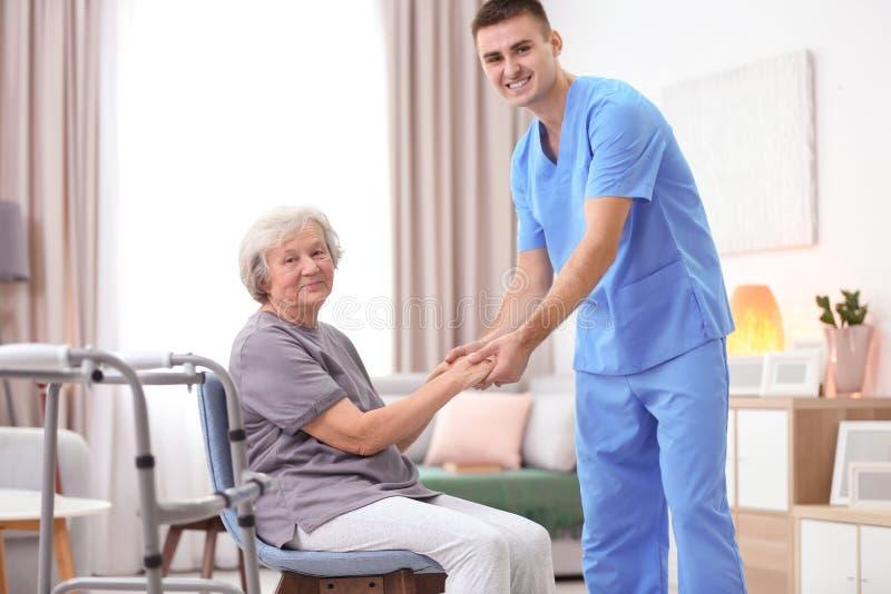 Mujer mayor que camina con ayuda del cuidador joven foto de archivo libre de regalías