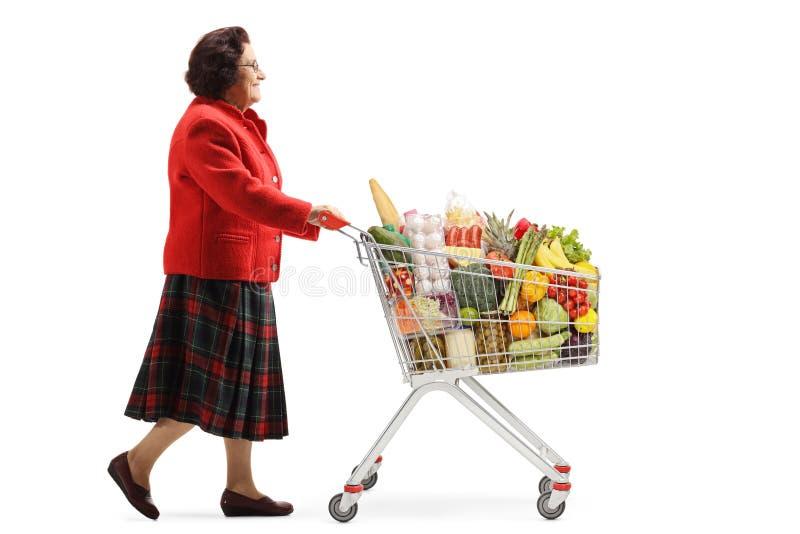 Mujer mayor que camina con un carro de la compra con los productos alimenticios imagenes de archivo