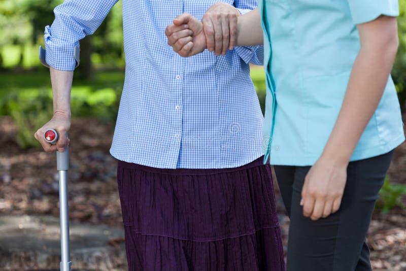 Mujer mayor que camina deteniendo a una enfermera imagenes de archivo