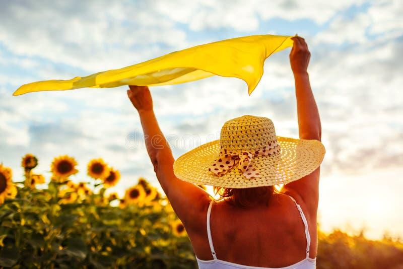 Mujer mayor que camina en el campo floreciente del girasol que aumenta las manos con la bufanda y que se divierte Vacaciones de v foto de archivo libre de regalías