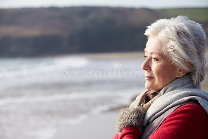 Mujer mayor que camina en la playa del invierno imagen de archivo