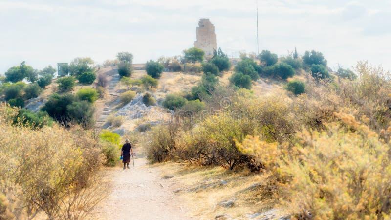 Mujer mayor que camina en la trayectoria por debajo el monumento antiguo en Atenas Grecia foto de archivo