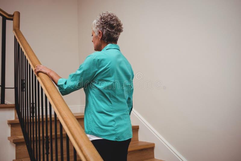 Mujer mayor que camina encima de las escaleras imagen de archivo libre de regalías