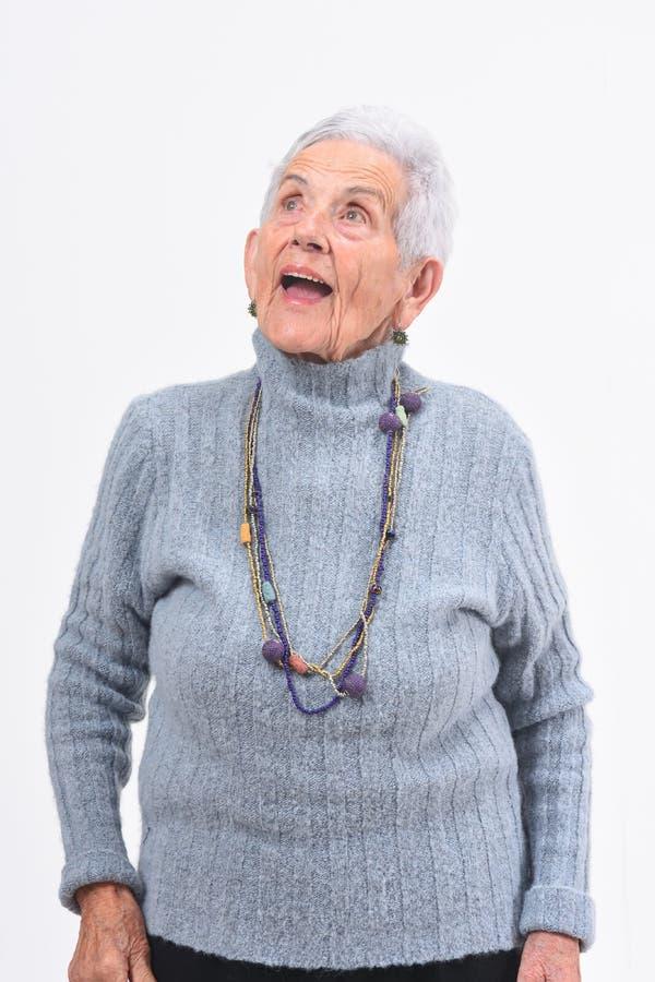 Mujer mayor que canta en un fondo blanco foto de archivo