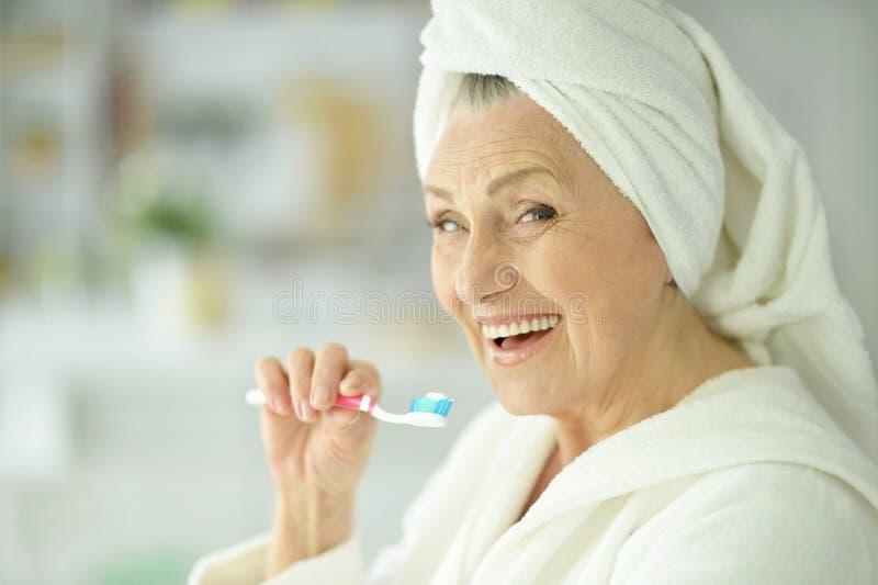 Mujer mayor que cepilla sus dientes foto de archivo