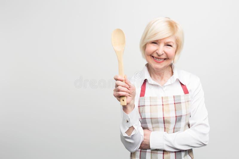 Mujer mayor que coloca y que sostiene una cuchara Ella es buena ama de casa Ella le gusta cocinar la comida sabrosa Aislado en bl imagen de archivo libre de regalías