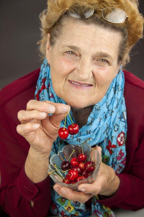Mujer mayor que come cerezas imagen de archivo libre de regalías