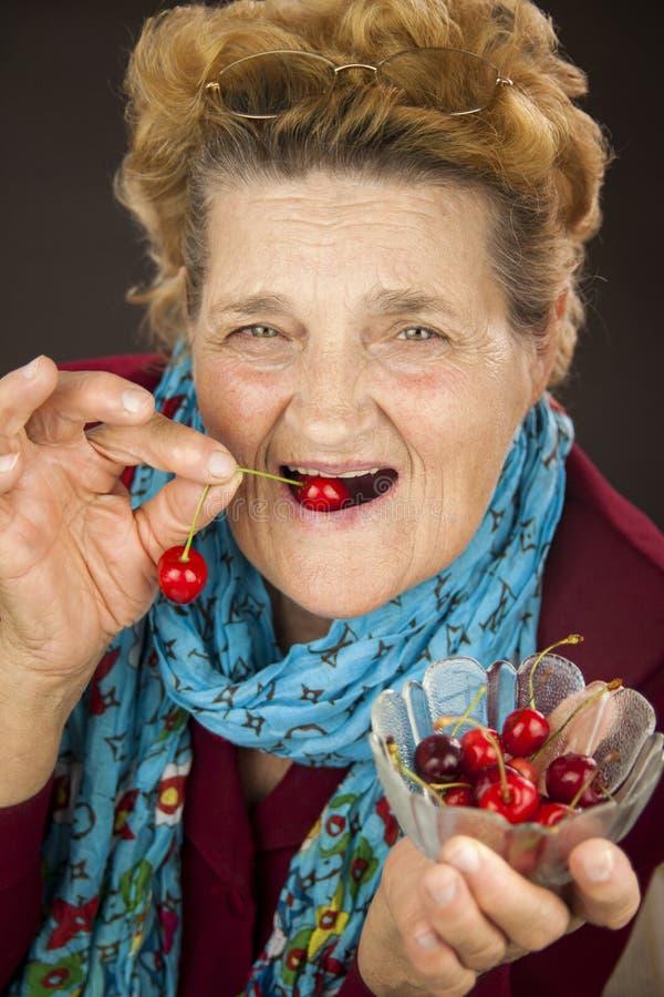 Mujer mayor que come cerezas imágenes de archivo libres de regalías