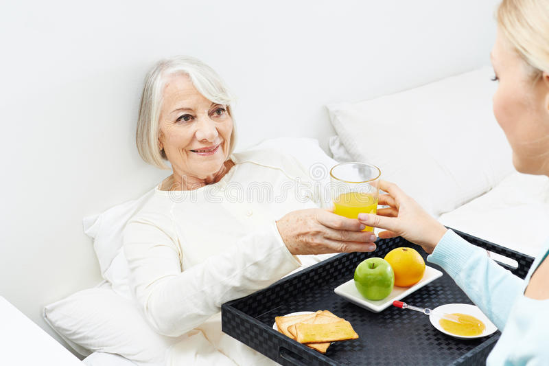 Mujer mayor que come el desayuno en cama foto de archivo libre de regalías