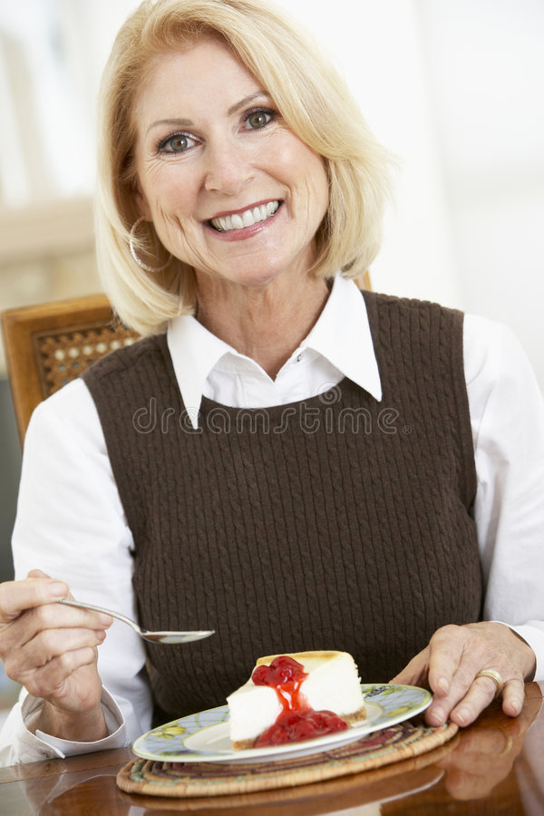 Mujer mayor que come el pastel de queso fotos de archivo libres de regalías