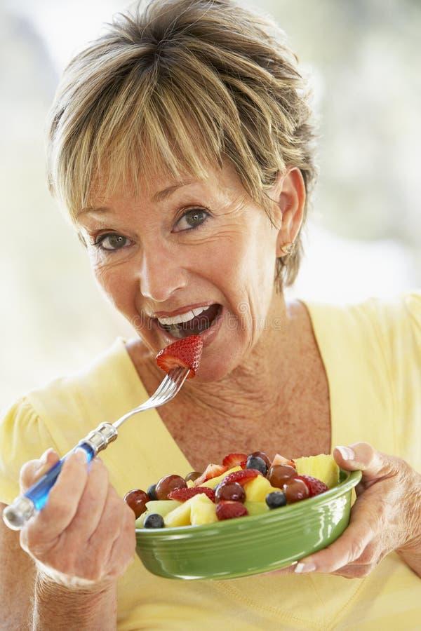 Mujer mayor que come la ensalada de fruta fresca foto de archivo libre de regalías