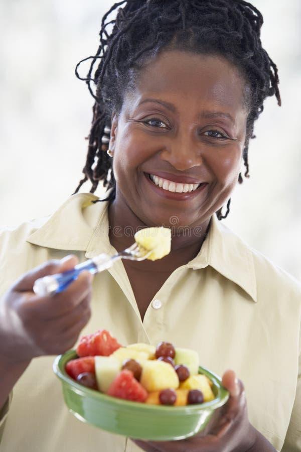Mujer mayor que come la ensalada de fruta fresca fotografía de archivo