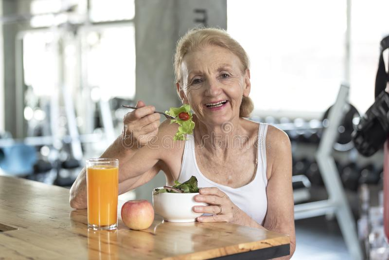 Mujer mayor que come la ensalada y el zumo de naranja sanos mayor fotos de archivo