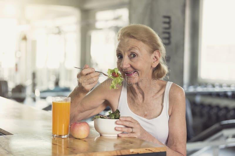 Mujer mayor que come la ensalada y el zumo de naranja sanos concepto mayor de la nutrición de la forma de vida de la salud fotos de archivo libres de regalías
