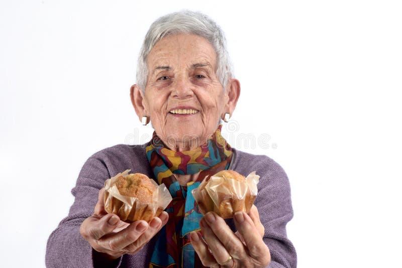 Mujer mayor que come la magdalena en el fondo blanco foto de archivo libre de regalías