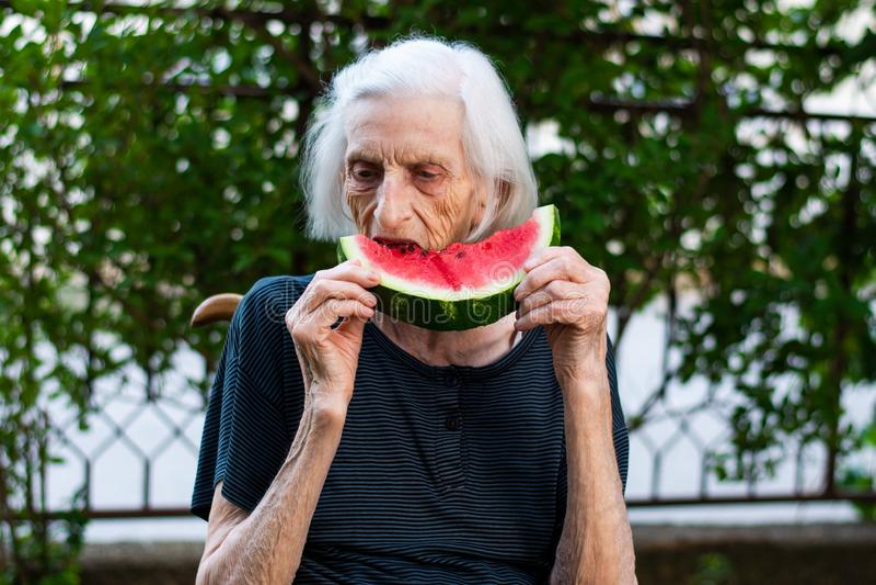 Mujer mayor que come la sand?a al aire libre imagen de archivo libre de regalías