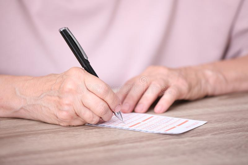 Mujer mayor que completa el boleto de lotería en la tabla fotografía de archivo
