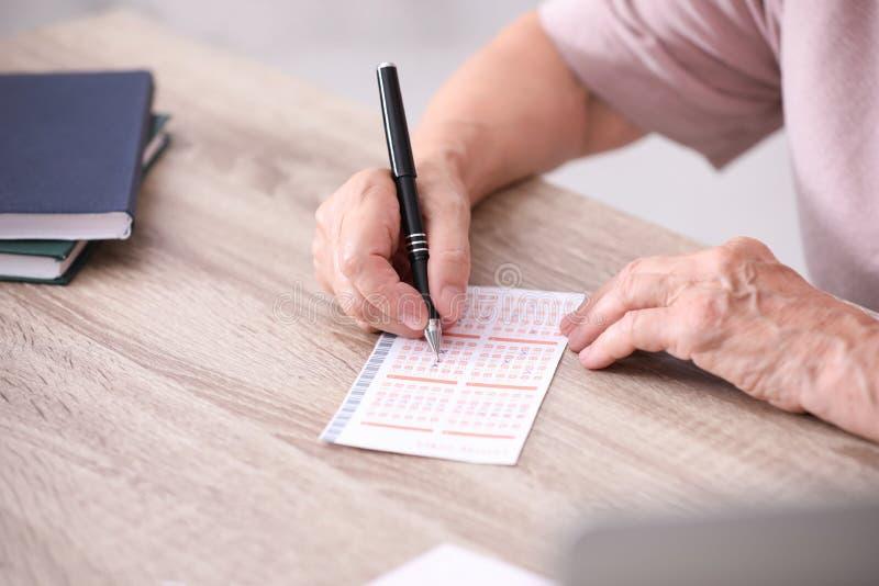 Mujer mayor que completa el boleto de lotería en la tabla, fotos de archivo