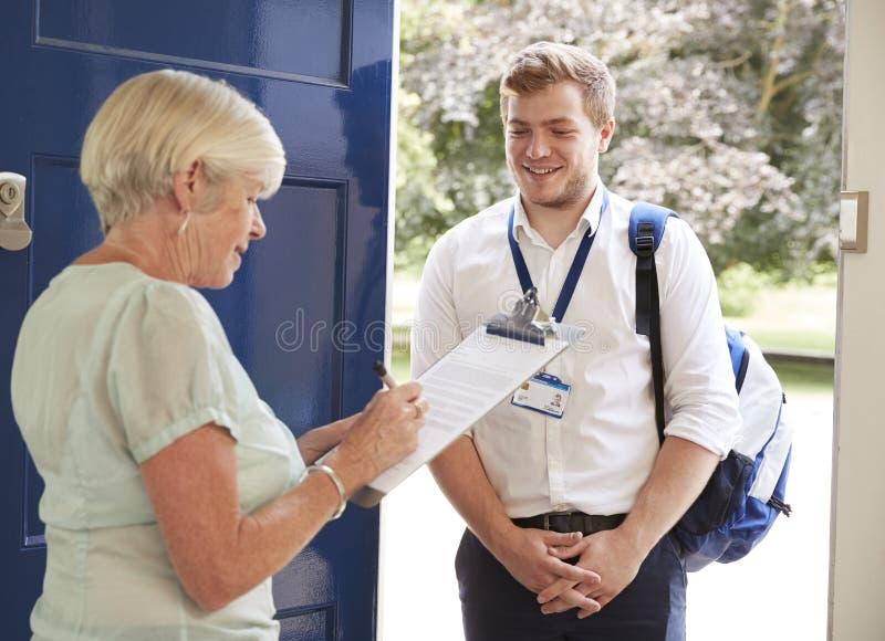 Mujer mayor que completa la encuesta para el visitante en su puerta principal fotografía de archivo