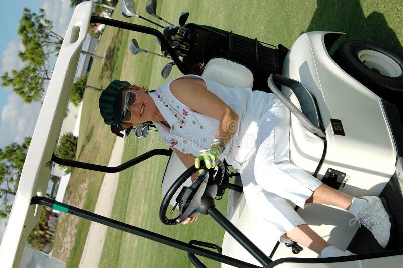 Mujer mayor que conduce el carro de golf
