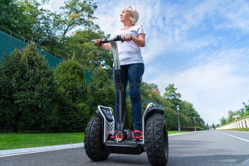 Mujer mayor que conduce el transportador personal eléctrico foto de archivo libre de regalías