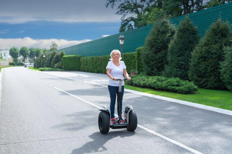 Mujer mayor que conduce el transportador personal eléctrico fotos de archivo