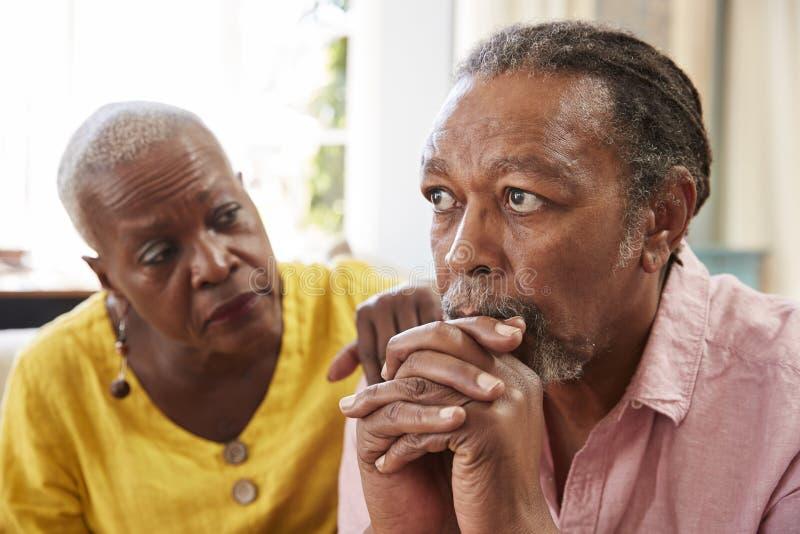 Mujer mayor que conforta al hombre con la depresión en casa imágenes de archivo libres de regalías