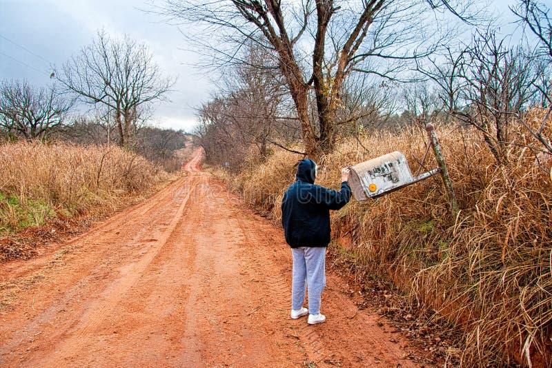 Mujer mayor que controla para saber si hay correo en una caja rural fotografía de archivo libre de regalías