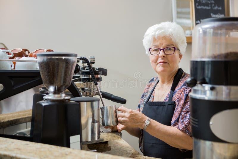 Mujer mayor que cuece la leche al vapor con la máquina de café express fotos de archivo